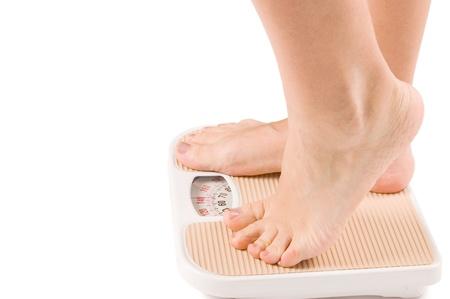 Female feet on scales isolated on white photo