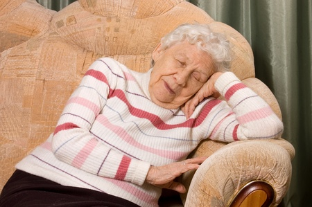sleeps: The elderly woman sleeps on a sofa