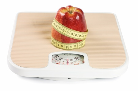 Scale, tape and apple on white photo
