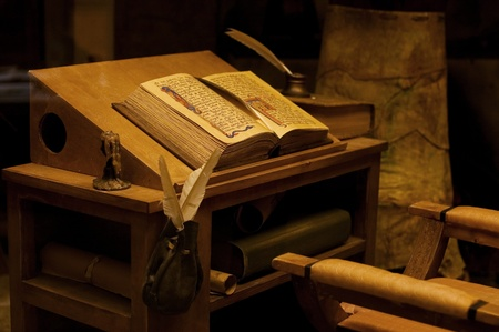 Table with the ancient book. vintage photo