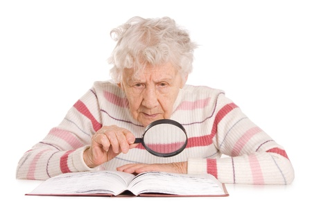 magnifier: The elderly woman reads the book