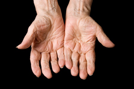 old beggar: Hands of the old woman on a black background