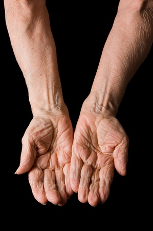 Hands of the old woman on a black background Stock Photo - 9457327