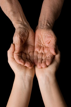 consoling: Hands of the old woman on a black background
