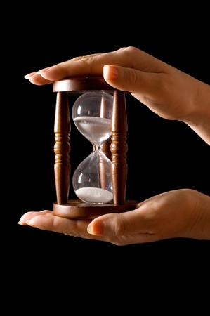 Hourglass in hands on a black photo