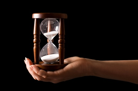 woman clock: Reloj de arena en manos de un negro Foto de archivo