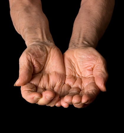 to beg: Hands of the old woman on a black background