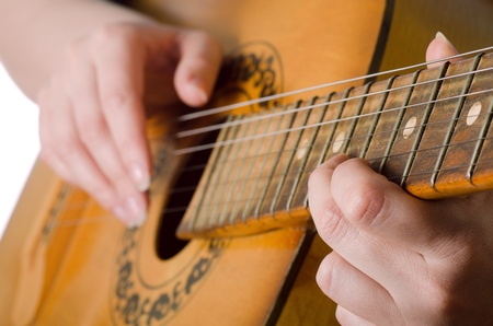 The woman plays an acoustic guitar photo