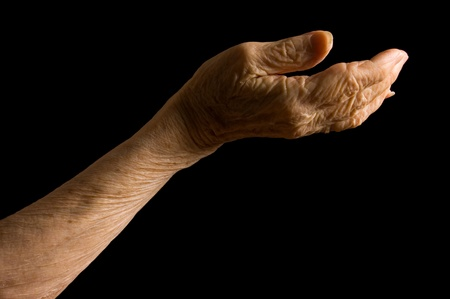 Hands of old woman on black background photo