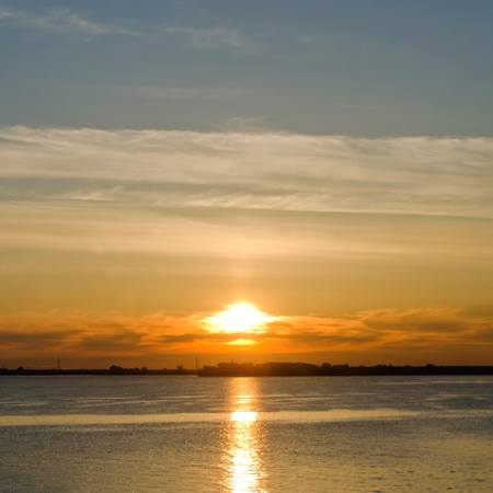 Sunset over the river in cloudy sky photo