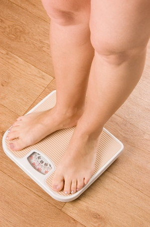 Female feet on scales on to floor photo