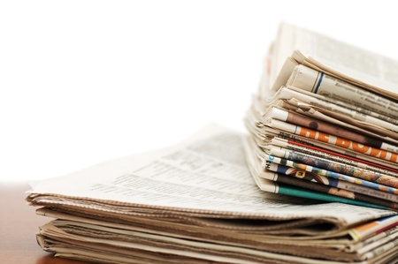 Heap of newspaper on a wooden table photo