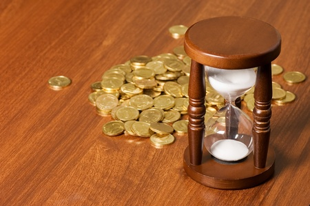 Hourglasses and coin On a wooden table photo