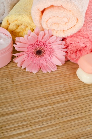 Pink gerbera and towel on bamboo rug photo