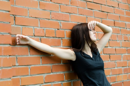 The young sad girl at brick walls Stock Photo - 10225483