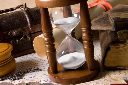 antique coins: Hourglass and the book - vintage concept