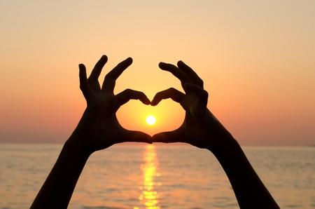 corazon en la mano: Silueta femenina contra una disminuci�n en el mar Foto de archivo