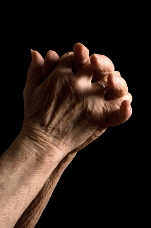 repentance: Hands of the old woman on black Stock Photo