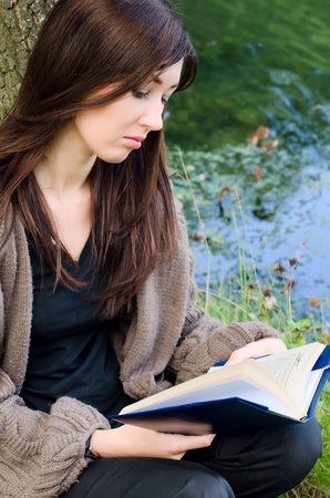 the long lake: Young girl with the book a pond Stock Photo