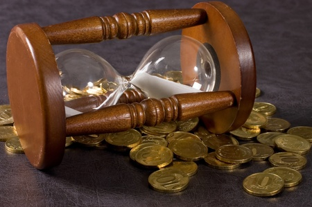 Hourglasses and coin On a grey background Stock Photo - 10831875