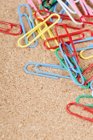 Closeup of multi-colored paper clips on corkboard photo