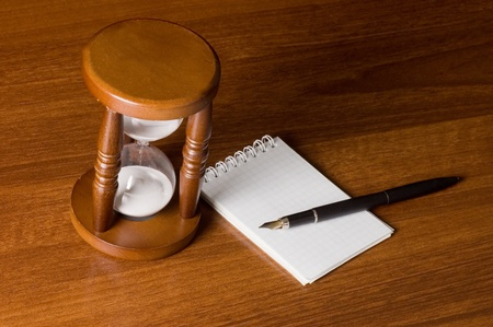 Hourglasses and Notebook on a wooden table photo