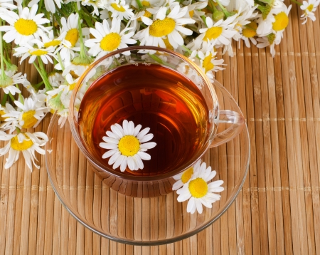 chamomile flower: Glass cup with fragrant a camomile tea