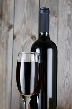 The red wine glass against wooden boards photo