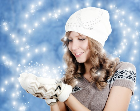 Beautiful girl in mittens on blue background Stock Photo