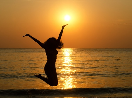 Silhouette of jumping girl against a decline Stock Photo - 11547970