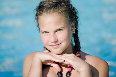 The beautiful smiling young  girl in pool photo