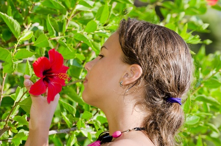 The young girl smells an exotic flower photo