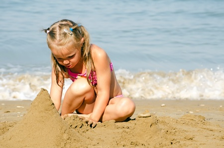 Little girl plays with sand sea coast photo
