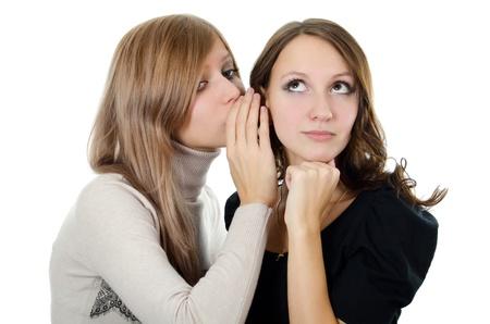 Two girl-friends tell gossips on an ear photo