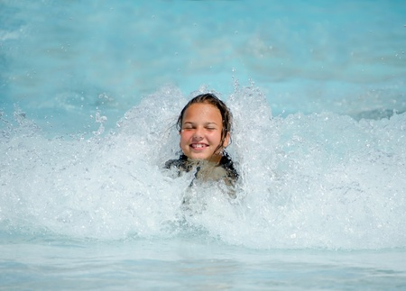 Young girl bathes in waves in pool photo