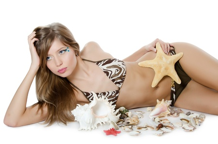 Young girl in bikini lays with seashells photo