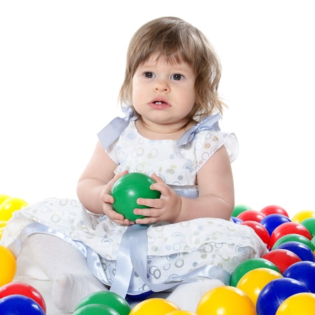 The little girl plays with multi-coloured balls isolated photo
