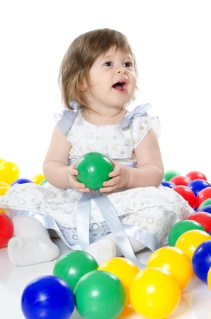 The little girl plays multi-coloured balls isolated photo