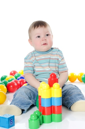 The little boy plays multi-coloured toys isolated Stock Photo - 12457889
