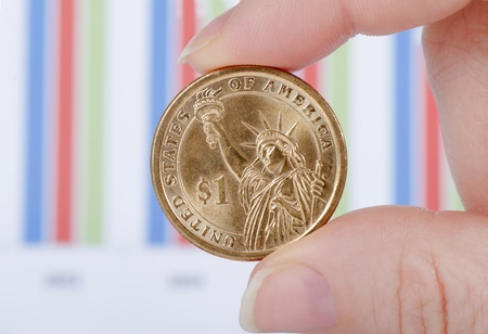Coins in hand against business of diagrammes photo