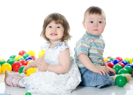 Little girl and boy plays multi-coloured balls photo