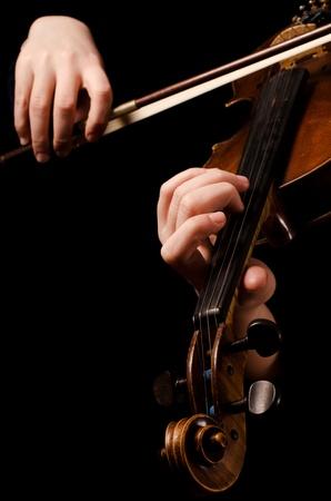 woman violin: Female hands play a violin on black