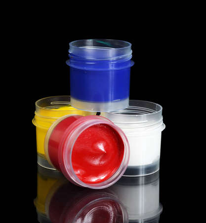 Jars with colour paints on black background photo