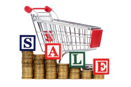 Coins in the form of the diagramme, shopping cart and word SALE photo