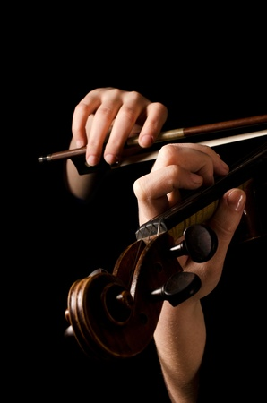 fiddles: Female hands play a violin on black