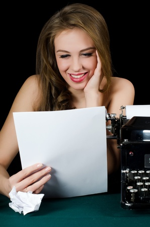 The beautiful girl at a typewriter. Retro photo