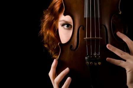 Beautiful girl with a violin on black photo