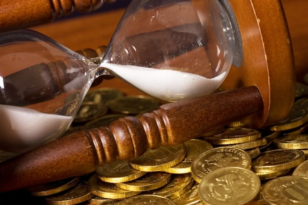Hourglasses and coin On a wooden table Stock Photo