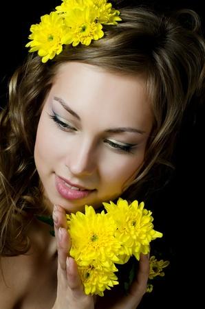 Girl with beautiful hair with yellow chrysanthemum photo