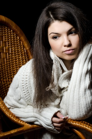 The beautiful girl in a wicker chair photo